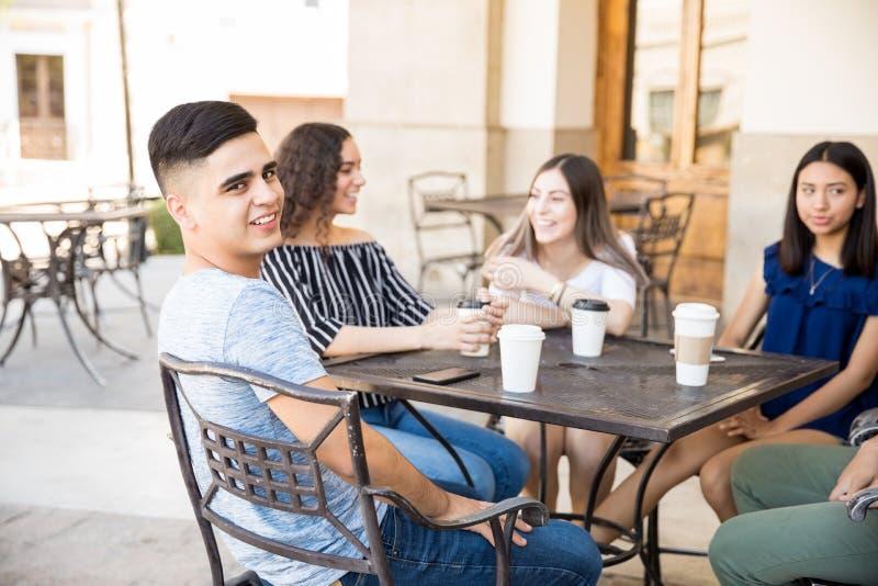 Menino novo que senta-se com os amigos no café exterior imagem de stock
