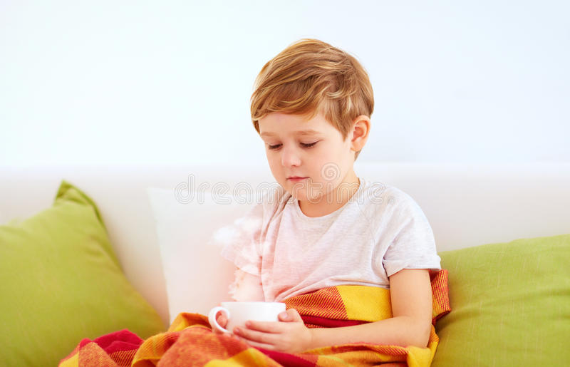 menino novo que senta-se em casa, aquecendo suas mãos em um copo do chá quente imagens de stock royalty free