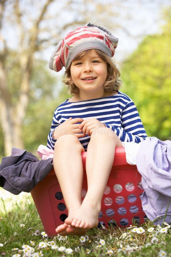 Menino novo que senta-se na cesta de lavanderia foto de stock royalty free