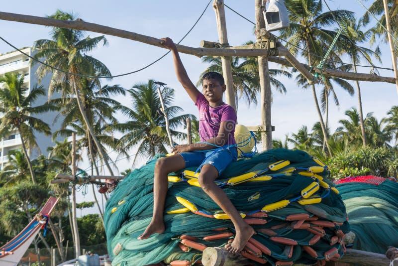 Menino novo que senta-se nas redes de pesca no barco fotografia de stock royalty free