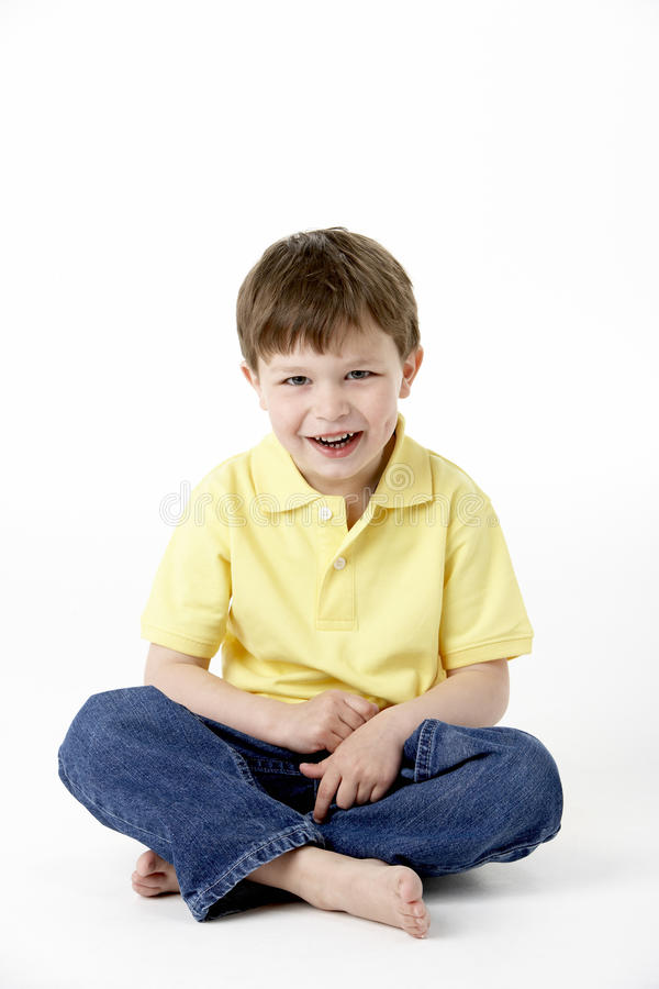 Menino novo que senta-se no estúdio fotografia de stock royalty free