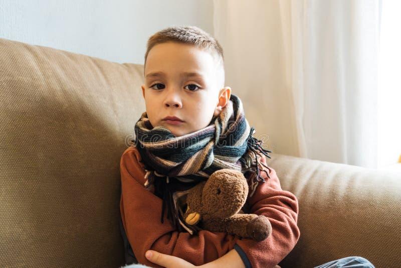 Menino novo que senta-se no sofá Doutor de espera da criança doente para visitá-lo Gripe, serviço pediatra em casa Conceito médic fotos de stock