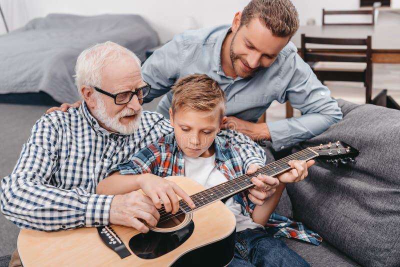 Menino novo que tenta aprender o jogo da guitarra quando seus pai e vovô forem fotografia de stock