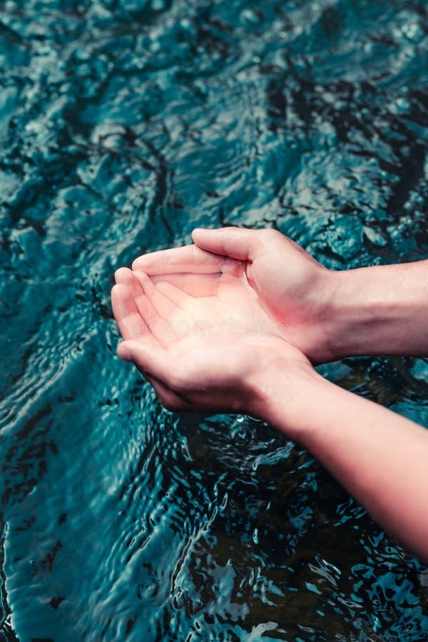 Menino novo que toma a água pura de um rio e que guarda a nas mãos imagens de stock royalty free