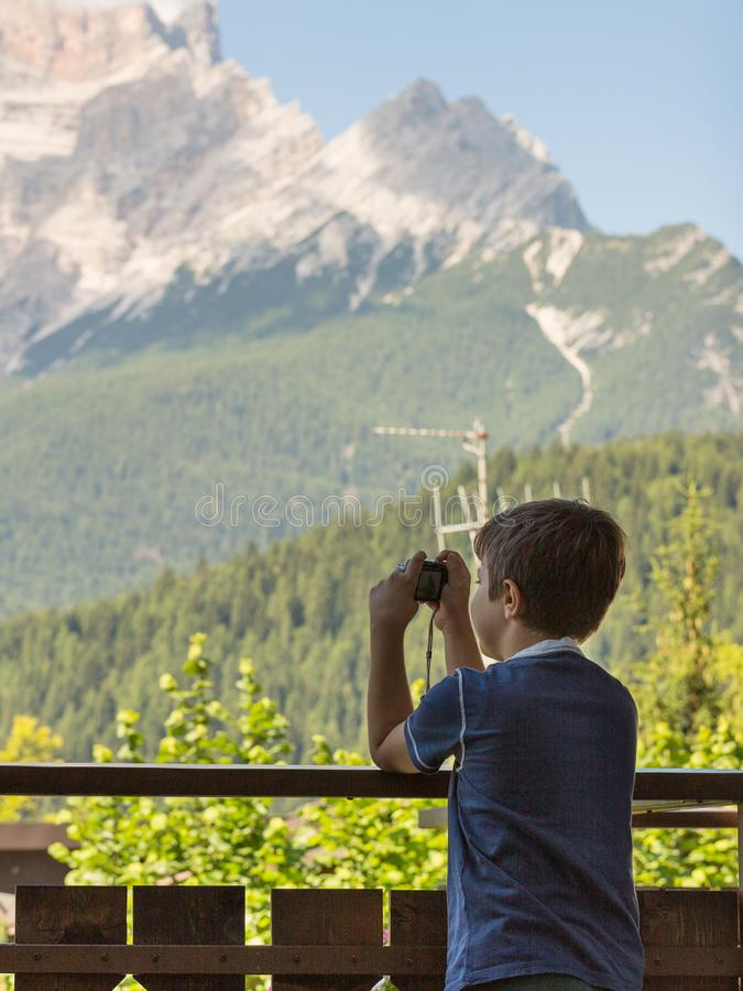 Menino novo que toma a foto com a câmera na montanha nas horas de verão fotografia de stock