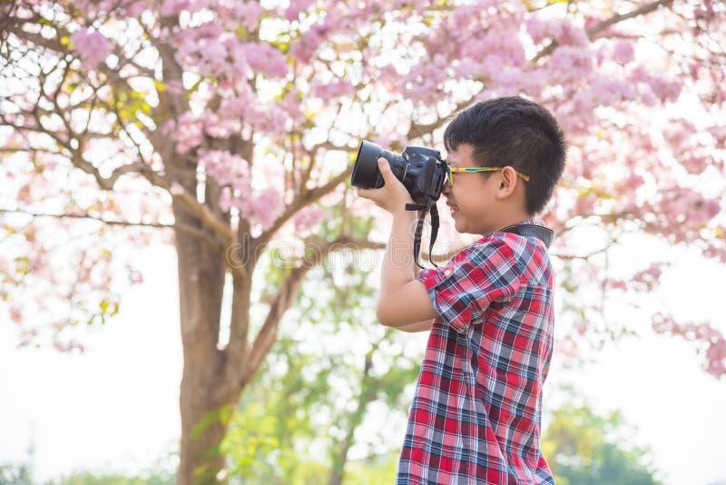 Menino novo que toma a foto pela câmera no parque fotografia de stock