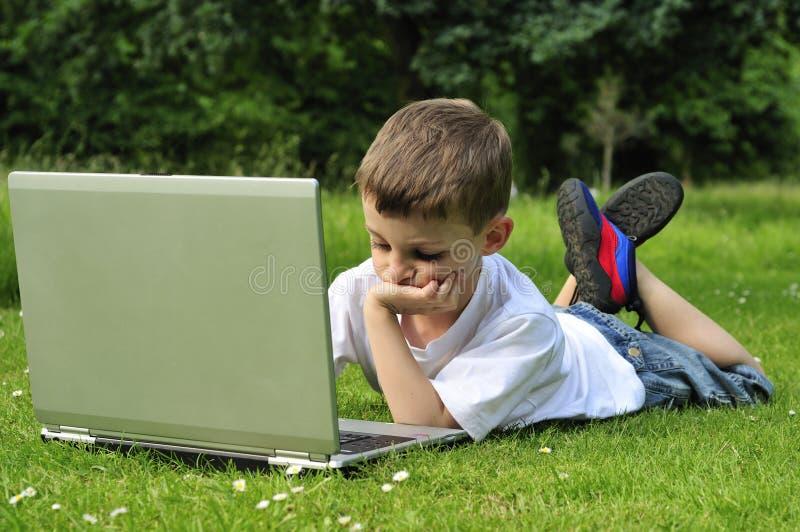 Menino novo que trabalha no portátil foto de stock royalty free