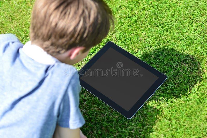 Menino novo que usa a tabuleta digital fora imagens de stock