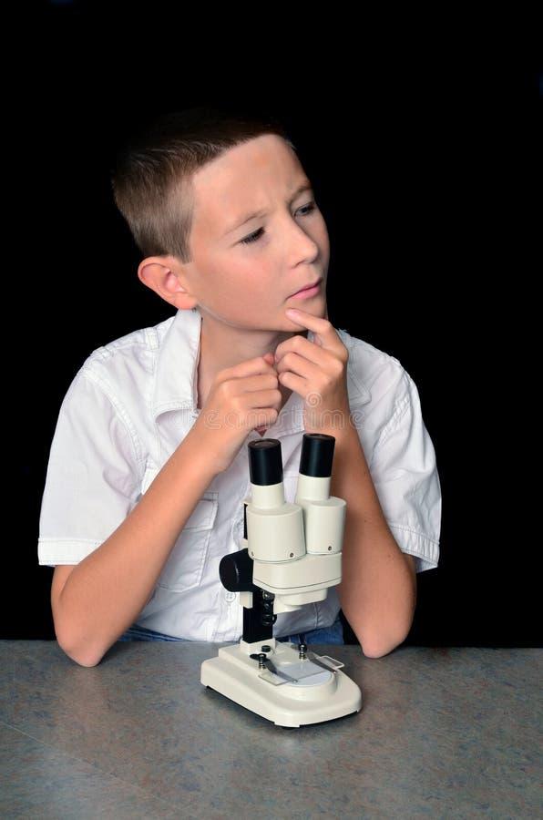Menino novo que usa um microscópio fotografia de stock