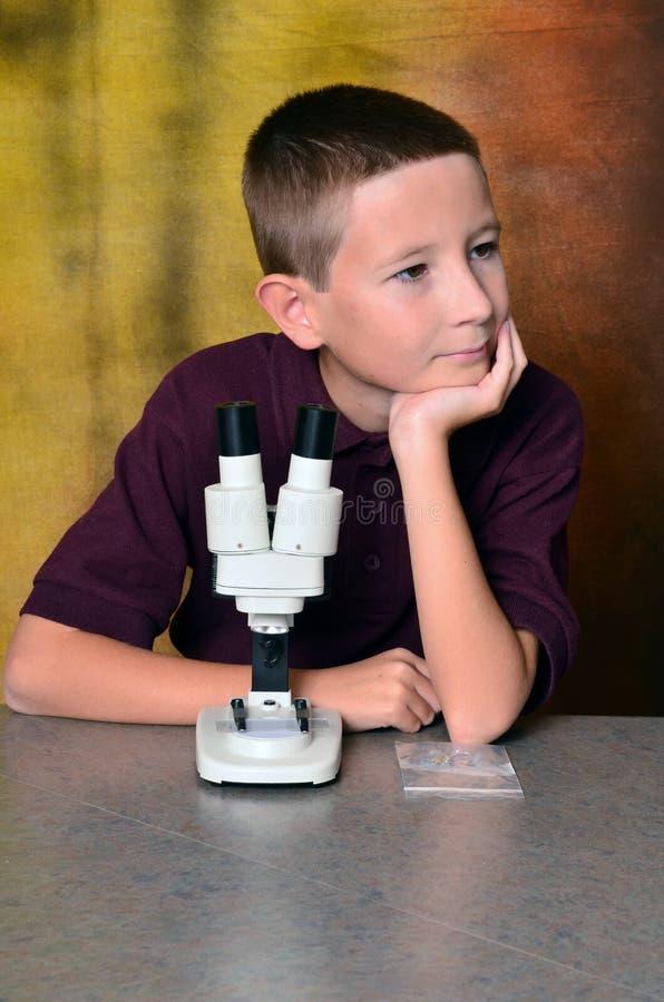Menino novo que usa um microscópio imagens de stock royalty free