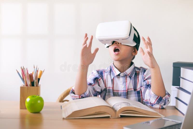 Menino novo que veste uns auriculares de VR Educação e conceito da tecnologia foto de stock royalty free