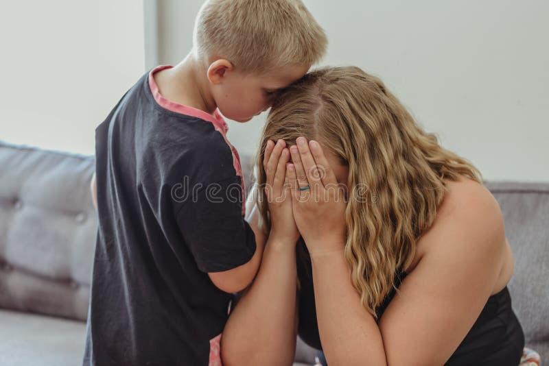 Menino novo referido para sua mãe e inclinação nela que consola a como grita imagens de stock