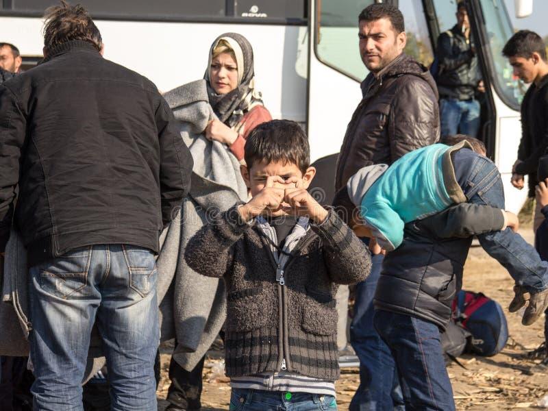 Menino novo, refugiado da criança, sorrindo e estando em um campo cercado por outros refugiados, perto da beira da Sérvia da Croá foto de stock