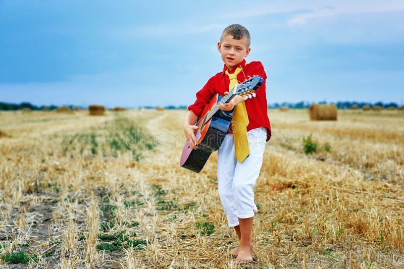 Menino novo romântico com a guitarra no campo fotografia de stock