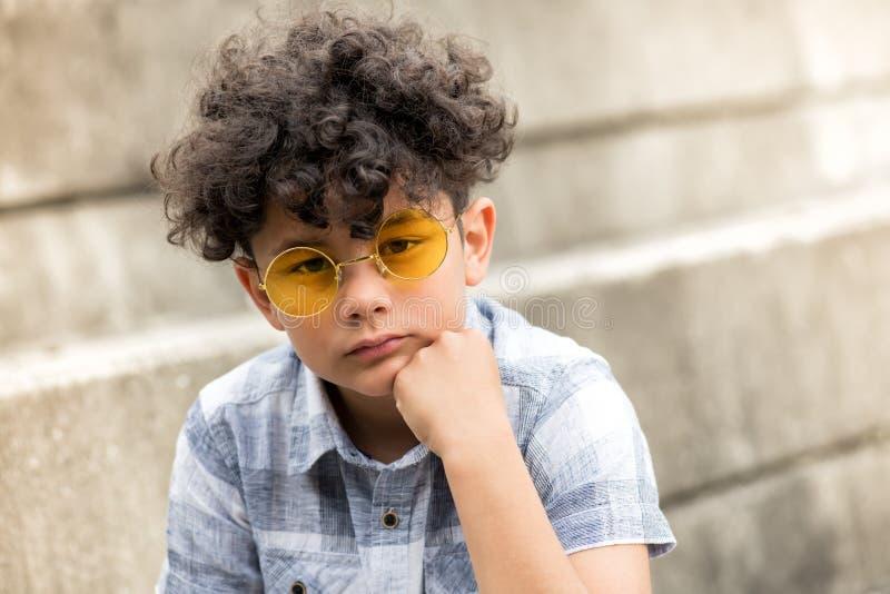 Menino novo sério em óculos de sol amarelos imagem de stock royalty free