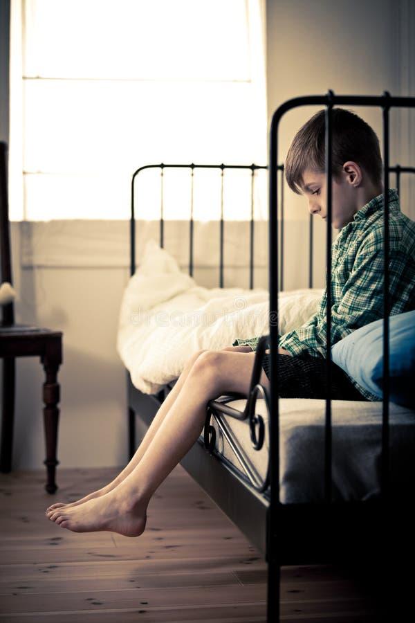 Menino novo só que senta-se na cama dentro de sua sala fotos de stock royalty free