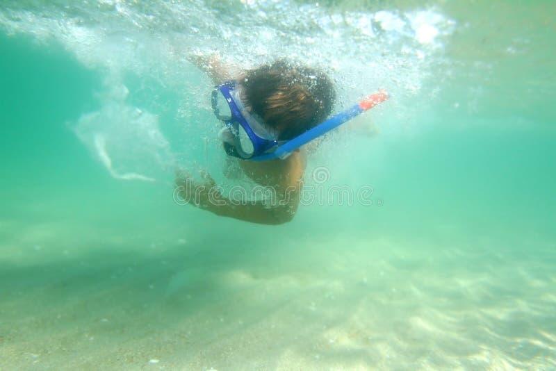 Menino novo subaquático no mar imagens de stock