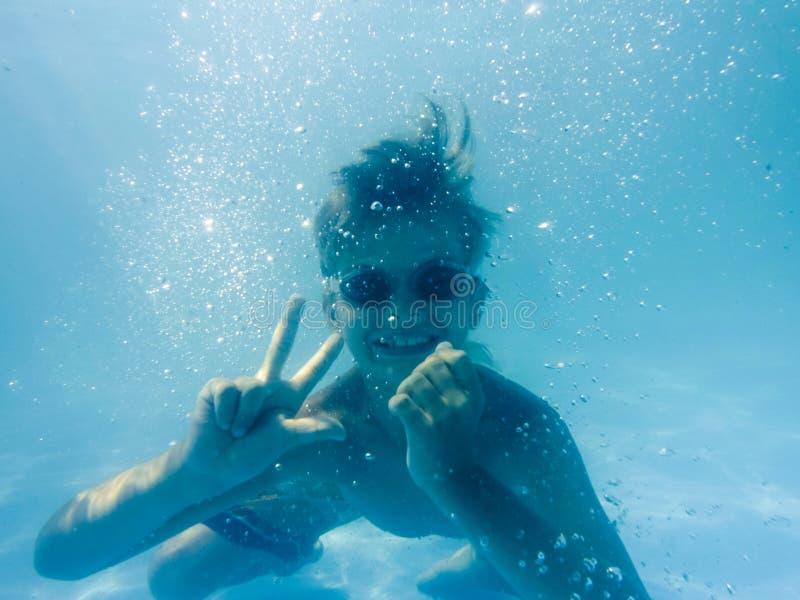 Menino novo subaquático que tem o divertimento fotografia de stock