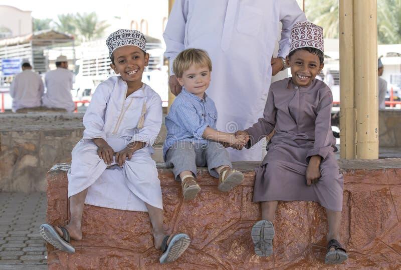 Menino omanense que faz amigos com menino europeu imagens de stock