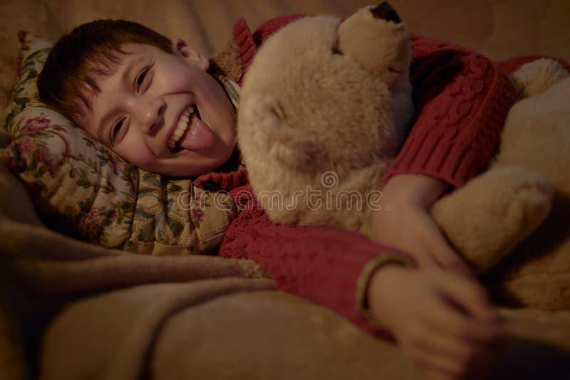 Menino para não dormir na cama e no divertimento ter com brinquedo do urso imagem de stock royalty free