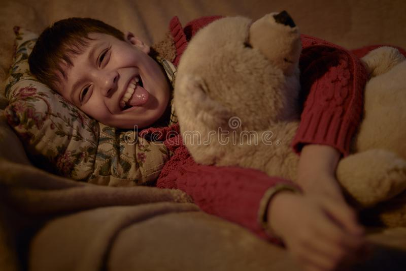 Menino para não dormir na cama e no divertimento ter com brinquedo do urso foto de stock royalty free