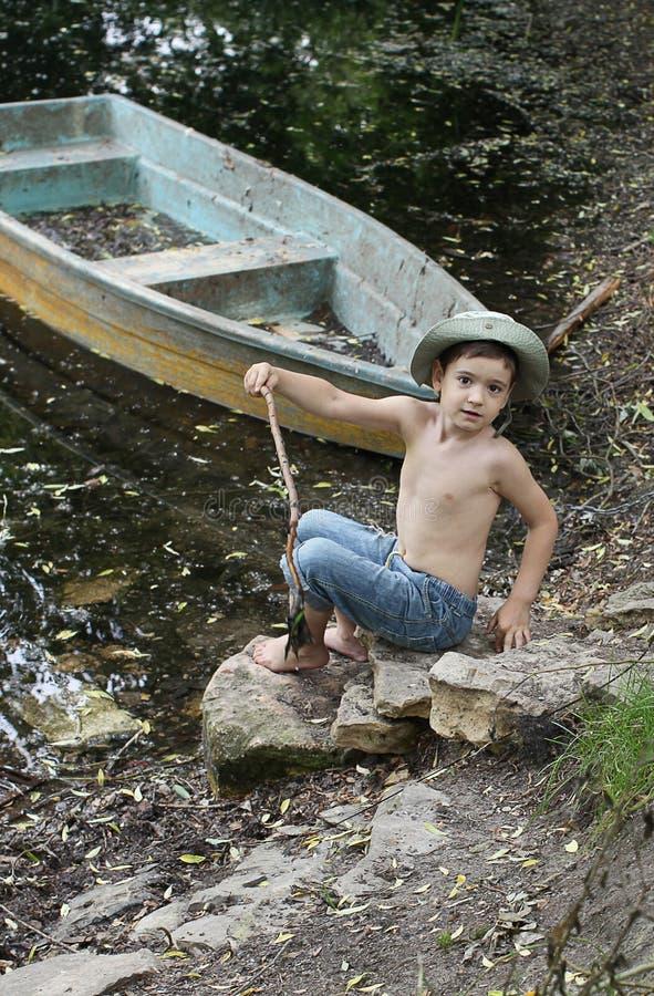 Menino pelo barco no lago foto de stock royalty free