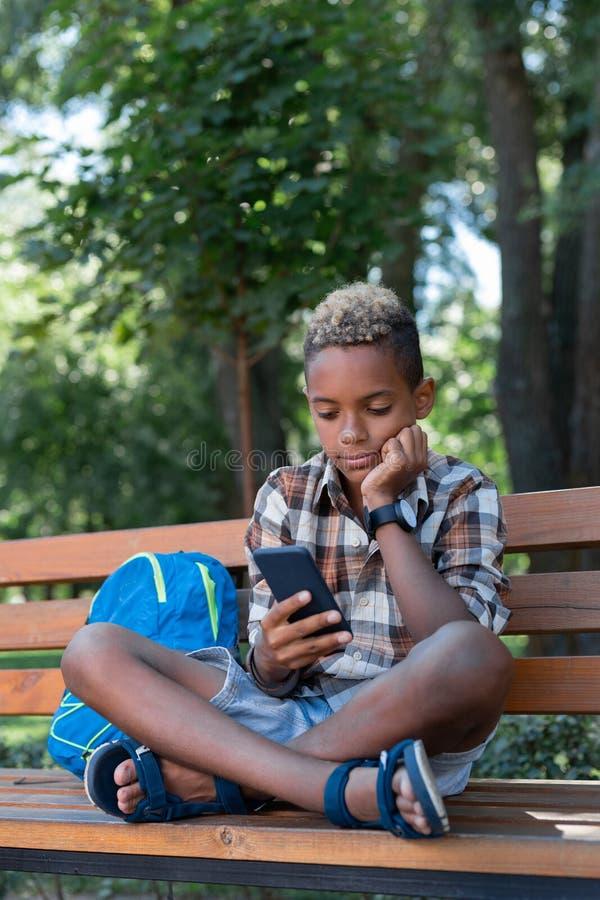 Menino pensativo agradável que usa seu smartphone novo imagem de stock royalty free