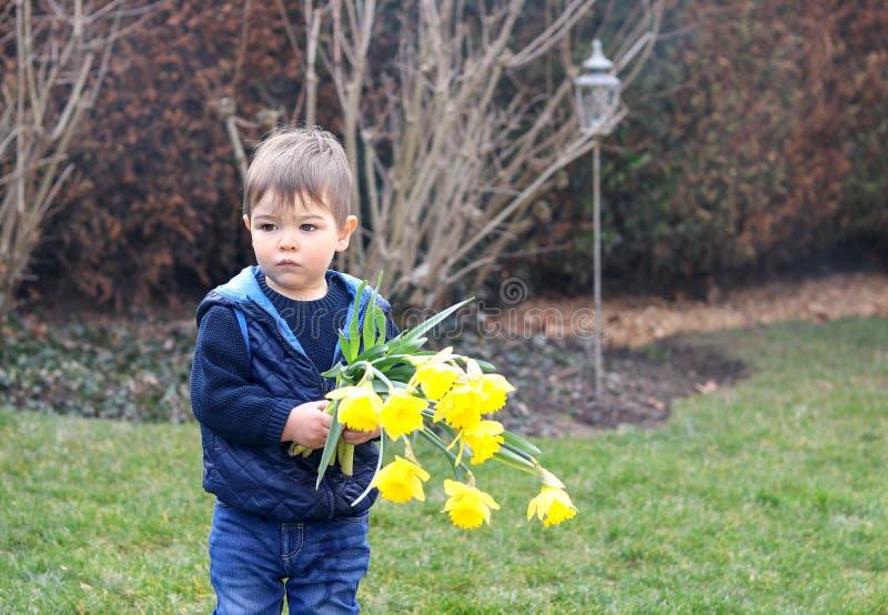 Menino pensativo pequeno bonito no ramalhete azul da terra arrendada da veste de flores amarelas brilhantes dos narcisos amarelos imagens de stock royalty free