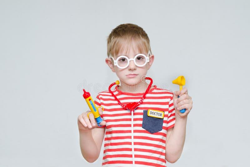 Menino pensativo que joga o doutor Seringa, vidros e phonendosco do brinquedo fotografia de stock