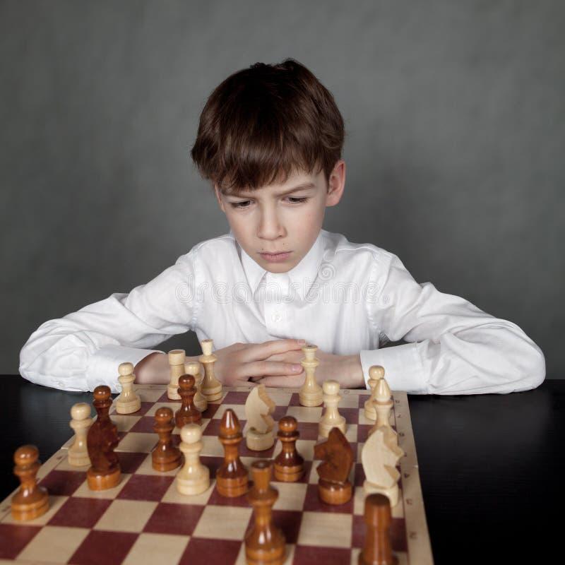 Menino pensativo que joga a xadrez, estúdio imagem de stock