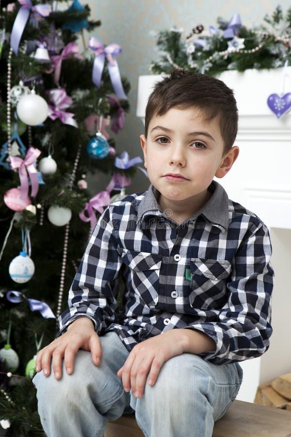Menino pensativo que senta-se perto da árvore de Natal fotos de stock