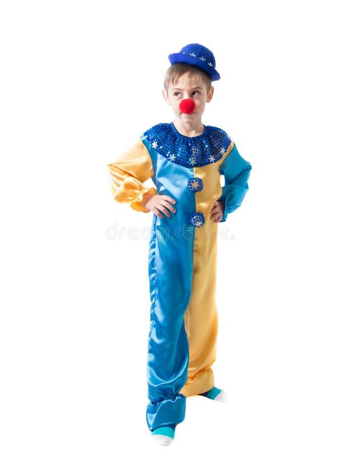 Menino pensativo vestido como um palhaço com um nariz vermelho que guarda as mãos em flancos e que olha ao lado fotos de stock