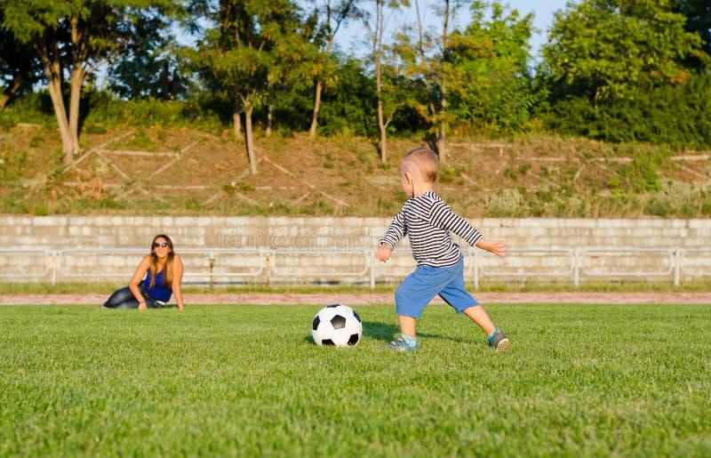 Menino pequeno atlético que joga o futebol foto de stock