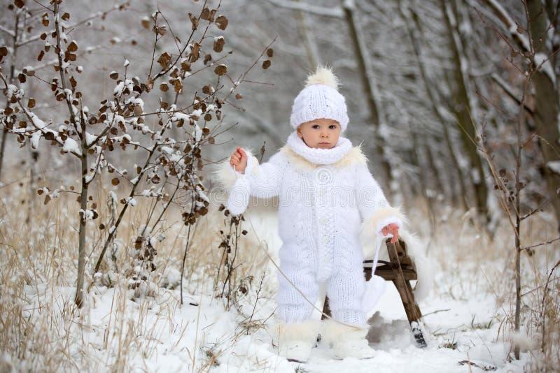 Menino pequeno bonito da criança e seus irmãos mais idosos, jogando fora com neve em um dia de inverno fotos de stock royalty free