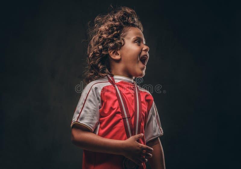 Menino pequeno bonito do campeão no sportswear com medalha de ouro que aprecia a vitória em um fundo textured escuro foto de stock royalty free