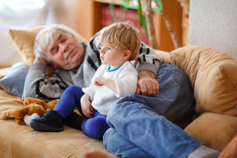 Menino pequeno bonito e avô da criança que olham junto o programa televisivo Neto do bebê e assento aposentado feliz do homem sup foto de stock