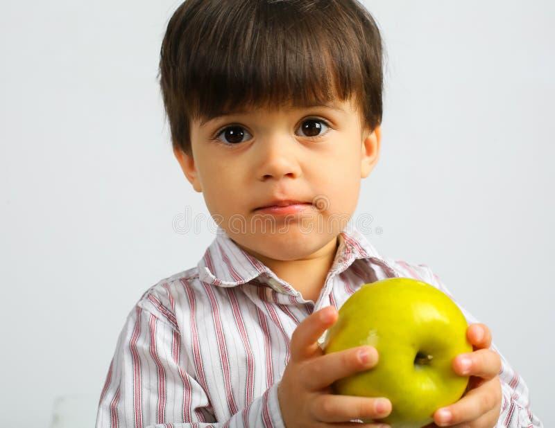 Menino pequeno bonito que come a ma?? verde fotos de stock