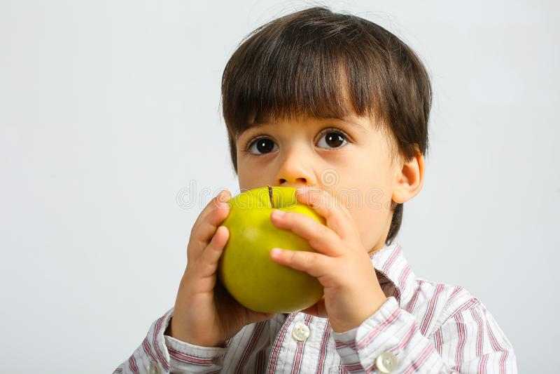 Menino pequeno bonito que come a ma?? verde foto de stock
