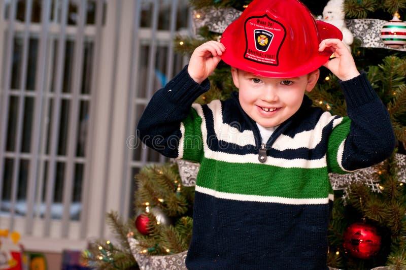 Menino pequeno com um chapéu do bombeiro fotografia de stock