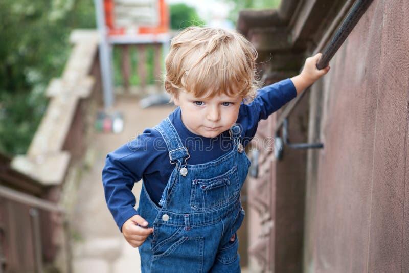 Menino pequeno da criança que escala escadas grandes na cidade imagens de stock royalty free