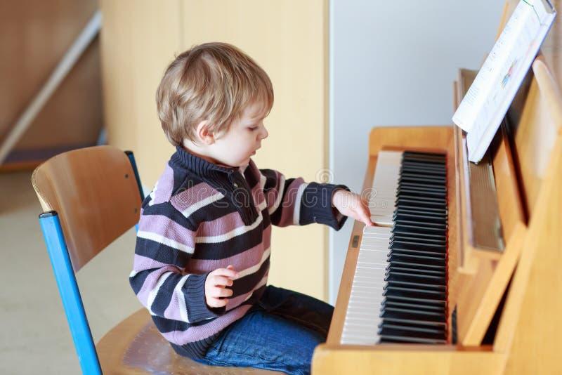 Menino pequeno da criança que joga o piano na escola de música. imagens de stock royalty free