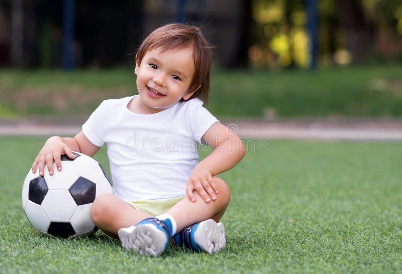 Menino pequeno da criança que senta-se com os pés cruzados no campo de futebol no dia de verão com bola de futebol Crian?a ativa  fotografia de stock royalty free