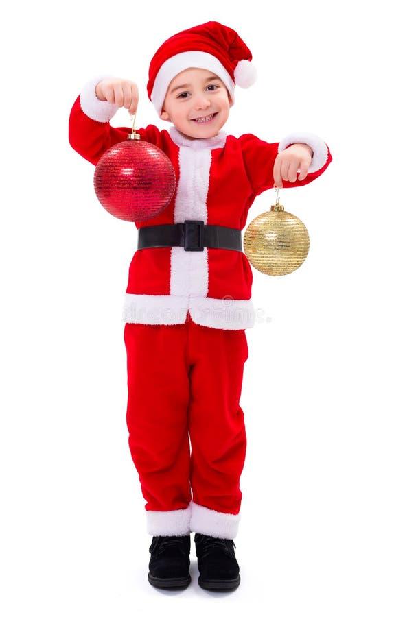 Menino pequeno de Santa Claus que mostra ornamento do Natal foto de stock