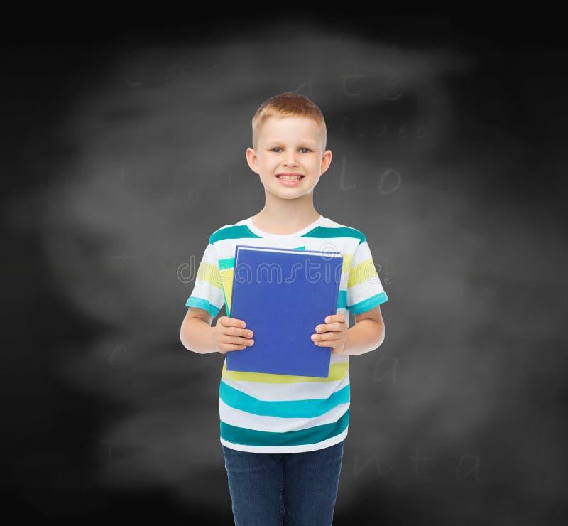 Menino pequeno de sorriso do estudante com livro azul imagem de stock royalty free