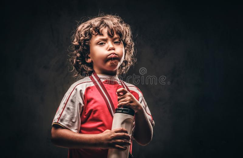 Menino pequeno do campeão no sportswear com uma água potável da medalha de ouro de uma garrafa em um fundo textured escuro foto de stock