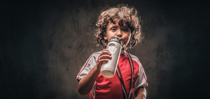 Menino pequeno do campeão no sportswear com uma água potável da medalha de ouro de uma garrafa em um fundo textured escuro imagens de stock royalty free