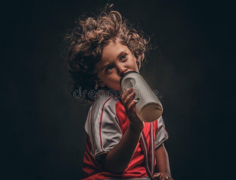 Menino pequeno do campeão no sportswear com uma água potável da medalha de ouro de uma garrafa em um fundo textured escuro imagens de stock