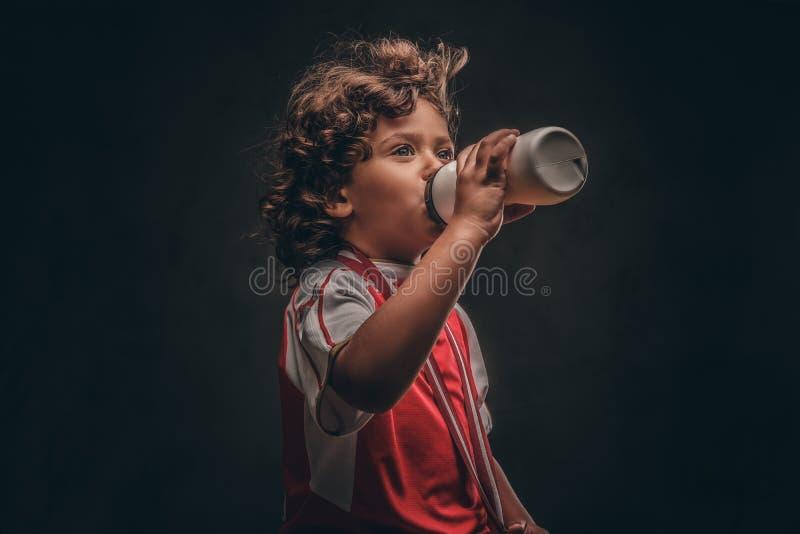 Menino pequeno do campeão no sportswear com uma água potável da medalha de ouro de uma garrafa em um fundo textured escuro fotografia de stock royalty free