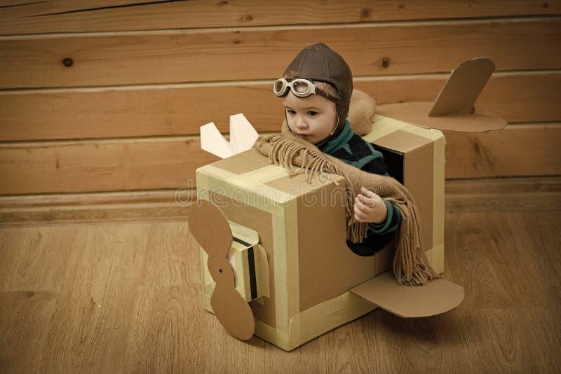 Menino pequeno do sonhador que joga com um avião do cartão imagens de stock royalty free