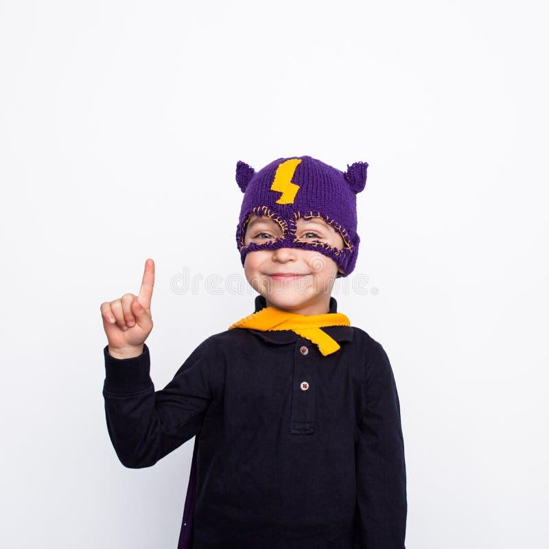Menino pequeno do super-herói que aponta acima fotos de stock royalty free